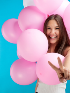 happy-girl-smiling-between-the-pink-baloons