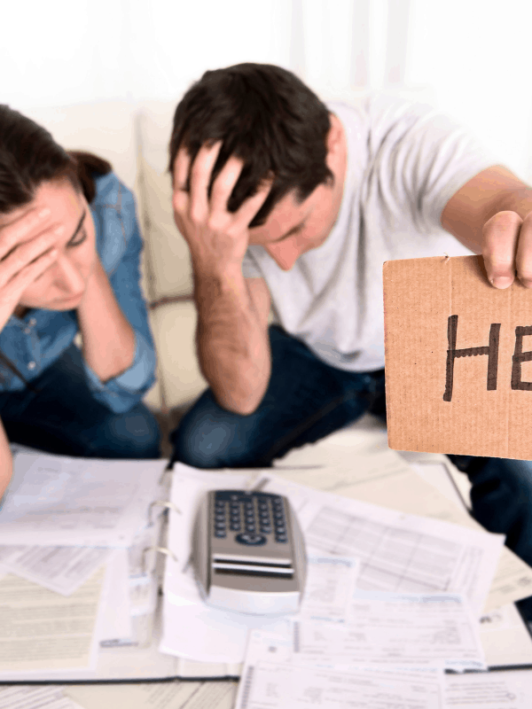 couple-holding-signs-help-pay-off-debts