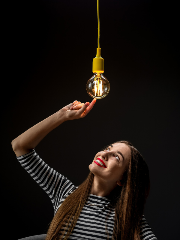 woman-smiling-touching-a-light-bulb