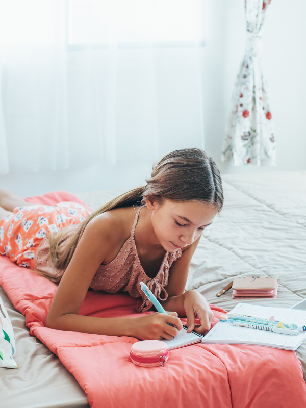 young-lady-writing-lying-in-bed
